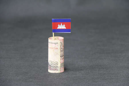 Rolled banknote money five hundred Cambodian Riel and stick with mini Cambodia flag on dark grey floor and background. Concept of financial business.