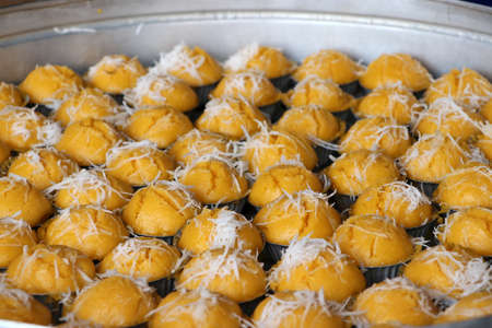 Steamed toddy palm cake in yellow color with white coconut, Thai sweet dessert. Stock Photo