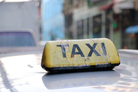 Taxi light sign or cab sign in yellow color with black text and tied with transparent tape on the car roof at the street blurred background, Myanmar.