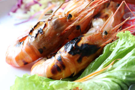 Two burnt prawn with green salad in the plate, two grilled shrimp with vegetable in the dish.