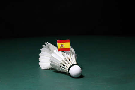 Mini Spain flag stick on used shuttlecocks on green floor of Badminton court with dark black background. Stock Photo