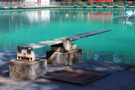 Springboard at the swimming pool. It is a strong, flexible board from which someone can jump in order to gain added impetus when performing a dive. Foto de archivo