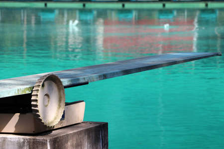 Springboard at the swimming pool. It is a strong, flexible board from which someone can jump in order to gain added impetus when performing a dive.
