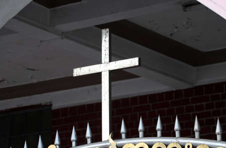Metal cross on the Iron fence. a representation of a cross with a figure of Jesus Christ on it.