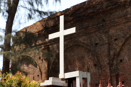 White metal cross on the Iron fence with out focus old brick background. Stockfoto