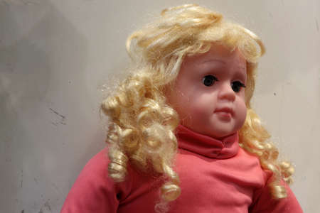 Girl doll with golden hair, wearing a red shirt. it is a small model of a human figure, often one of a baby or girl, used as a child's toy. 写真素材