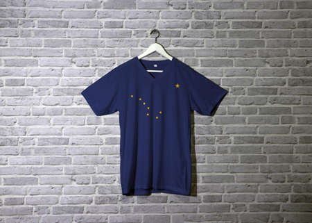 Alaska flag on shirt and hanging on the wall with brick pattern wallpaper. The states of America, eight gold stars on a blue background. Фото со стока