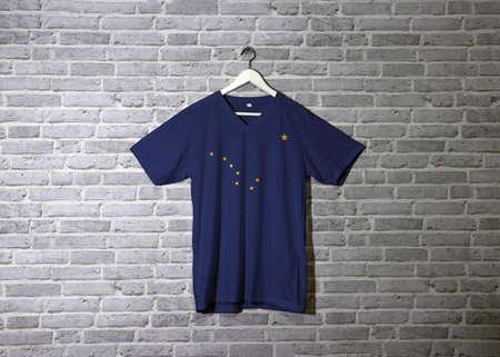 Bandera de Alaska en la camisa y colgada en la pared con papel tapiz de patrón de ladrillo. Los estados de América, ocho estrellas doradas sobre fondo azul. Foto de archivo