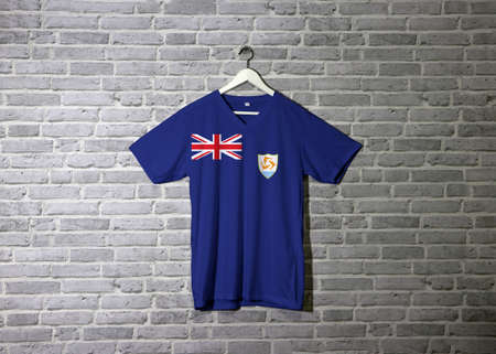 Anguilla flag on shirt and hanging on the wall with brick pattern wallpaper. British flag in the canton, charged with the coat of arms consists of three dolphins.