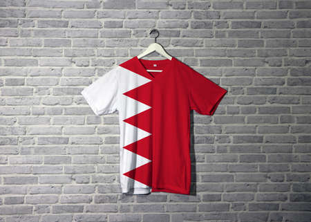 Bahrain flag on shirt and hanging on the wall with brick pattern wallpaper, five white triangles in the form of zigzag on red field.