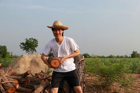 Man farmer standing and carrying timber beside the stack of firewood in the sugarcane farm and wearing a straw hat with white t-shirt. Stock Photo