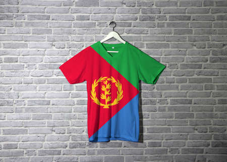 Eritrea flag on shirt and hanging on the wall with brick pattern wallpaper. Red triangle on blue and green triangle with olive branch on gold color.