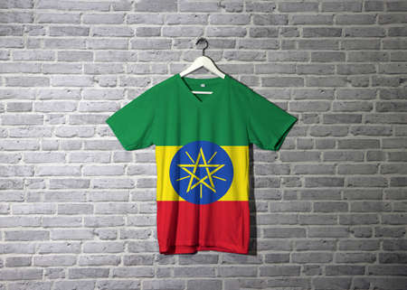 Ethiopia flag on shirt and hanging on the wall with brick pattern wallpaper, tricolor of green yellow and red with the National Emblem.