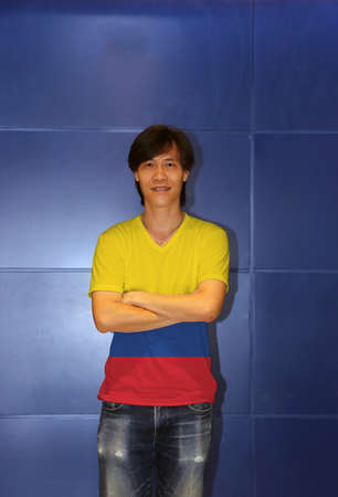 Man wearing Colombia flag pattern shirt and cross one's arm on the blue wall background, a horizontal tricolor of yellow (double-width) blue and red. 스톡 콘텐츠