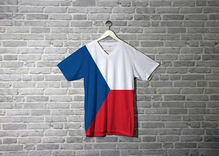Czech Republic flag on shirt and hanging on the wall with brick pattern wallpaper, two equal horizontal of white and red with a blue  triangle on the hoist side. 版權商用圖片 - 121845479