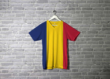 Chad flag on shirt and hanging on the wall with brick pattern wallpaper. A vertical tricolor of blue gold and red.
