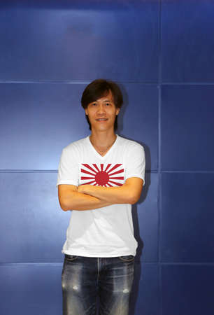 Man wearing war flag of the Imperial Japanese Army on white shirt and cross ones arm on the blue wall background, the rising sun flag on shirt.