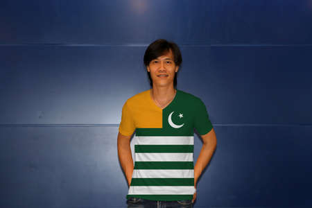 Man wearing Azad Kashmir flag on shirt and standing on the blue wall background. Green background with four white stripes; a gold canton and a star and crescent.