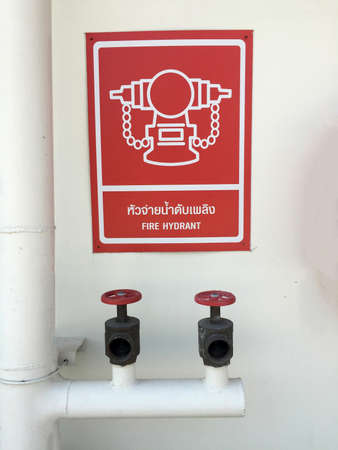 water pipe and water valve with red and white sigh symbol of fire hydrant with text in English and Thai on the wall. 版權商用圖片