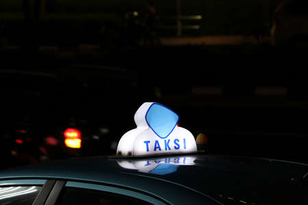 Taxi light sign or cab sign in blue and white color on the car roof at the street in the dark night, With text TAKSI in Indonesia.
