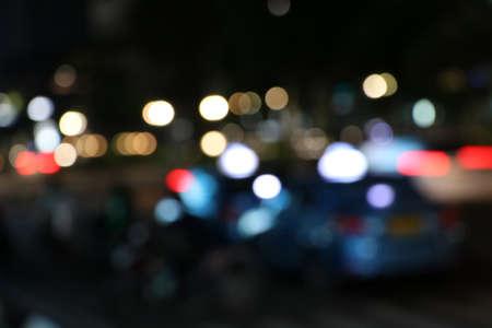 暗闇の中で抽象的なぼやけたカラフルな照明。夜に暖かいカラフルなライトと抽象的なボケの背景。