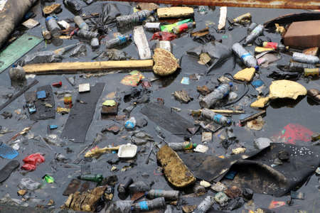Trash and garbage floating on the surface of the water. Plastic waste and foam dumped into the water, causing sewage.