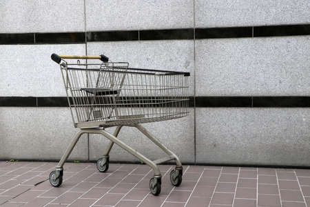 Shopping Cart on the floor with grey and horizontal black line background. trolley is a cart supplied by a shop, especially supermarkets, for use by customers inside the shop for transport of merchandise to the checkout counter during shopping.