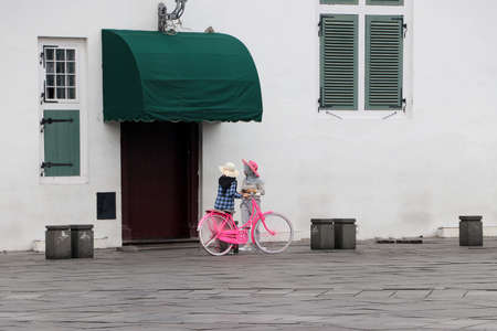 Jakarta, Indonesia May 6, 2019: Two Muslim women Indonesian with pink bicycle beside the door window and wall in the Fatahillah Square at old town neighborhood in Jakarta. Editorial