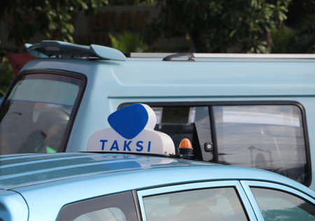 Taxi light sign or cab sign in blue and white color on the blue color of car roof at the street, With text TAKSI in Indonesia.