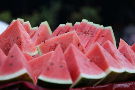 Watermelon cut into triangular pieces, put together. the smooth green skin with red pulp and watery juice.