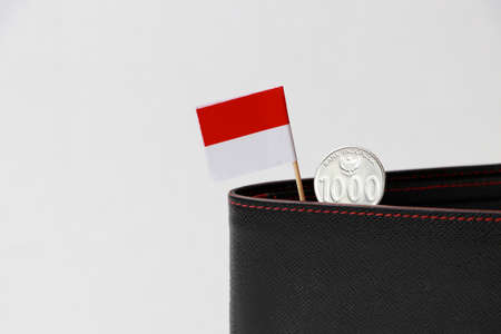One thousand Rupiah with mini Indonesia flag stick on the black wallet on white background. Concept of finance or currency.
