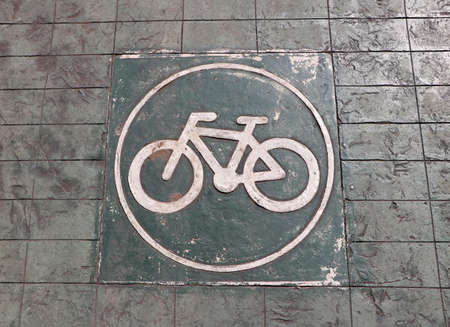 The white bicycle in the circle painting on the green bike lane. it is a division of a road marked off with painted lines, for use by cyclists. Stok Fotoğraf