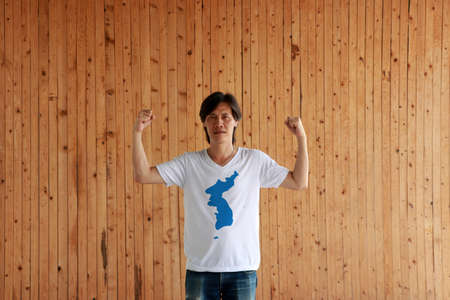 Man wearing Unification Korea flag color of shirt and standing with raised both fist on the wooden wall background. Korean Peninsula in blue on white.