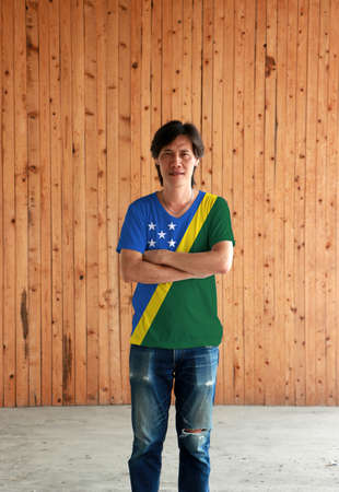 Man wearing Solomon Islands flag color shirt and cross one's arm on wooden wall background, a thin yellow narrow diagonal stripe divided diagonally with green and blue triangle and star.
