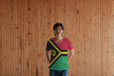 Man wearing Vanuatu flag color of shirt and standing with crossed behind the back hands on the wooden wall background, red and green with black and yellow color boar's tusk encircling two crossed fern fronds and the golden pall.