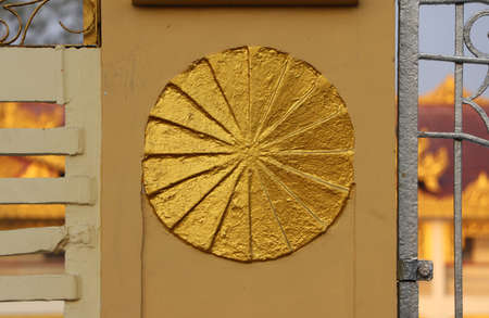 Gold painted stucco circle on the fence, symbolic of Dharma wheel.
