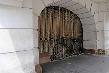 Old bicycle parking in front of the arched door.