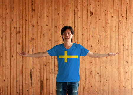 Man wearing Sweden flag color shirt and standing with arms wide open on the wooden wall background, consists of a yellow or gold Nordic Cross on a field of blue.