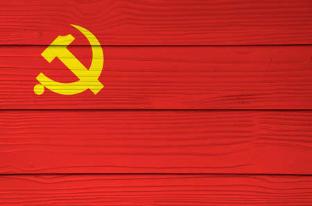 Chinese Communist Party flag color painted on Fiber cement sheet wall background, golden hammer and sickle on red color. Stock Photo