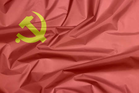 Fabric flag of Democratic Kampuchea, golden hammer and sickle on red color.