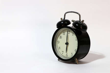 Twin bell alarm clock black color on six oclock put oblique on the white floor.