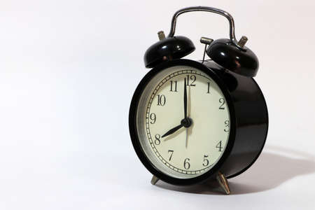 Twin bell alarm clock black color on eight oclock put oblique on the white floor.