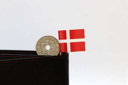 One coin of Danish Kroner money and mini Denmark flag stick on the black wallet with white background. Concept of finance or currency.