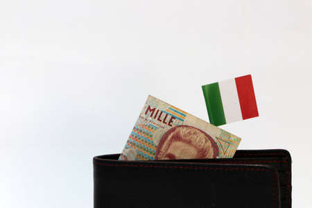 One thousand Lire of Italy banknote and mini Italia nation flag stick on the black wallet with white background. Concept of finance or currency.