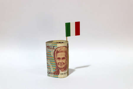 Rolled banknote money one thousand Lire Italy and stick with mini Italia nation flag on white background. Concept of financial business. Archivio Fotografico