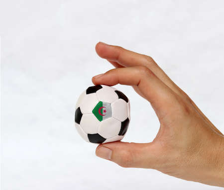 Mini ball of football in hand and one black point of football is Algeria flag, hold it with two finger on white background. Concept of sport or the game in handle or minor matter. 免版税图像