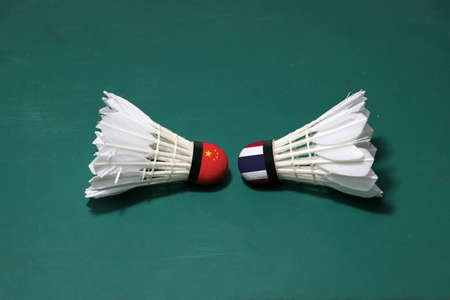 Two used shuttlecocks on green floor of Badminton court with both head each other. One head painted with Chinese flag And one head painted with the Thai flag, concept of badminton competition between the two countries.