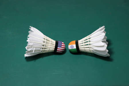Two used shuttlecocks on green floor of Badminton court with both head each other. One head painted with USA flag and one head painted with the India flag, concept of badminton competition.