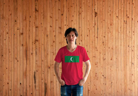 Man wearing Maldives flag color shirt and standing with two hands in pant pockets on the wooden wall background, green with red border and white crescent on center.