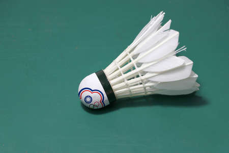 Used shuttlecock and on head painted with Chinese Taipei flag put horizontal on green floor of Badminton court. Badminton sport concept.
